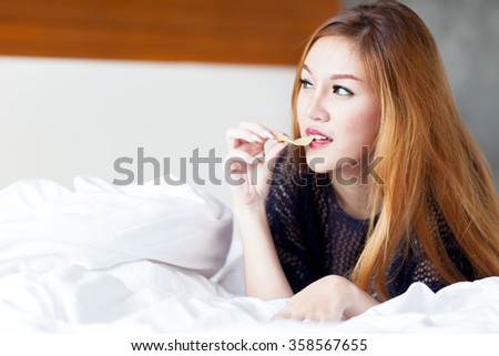 woman eating potato chips in bed at home - stock photo