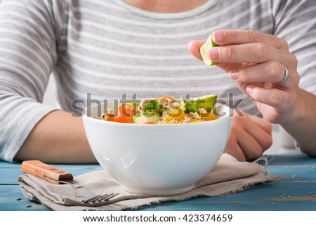 Woman eating quinoa and vegetables  - stock photo