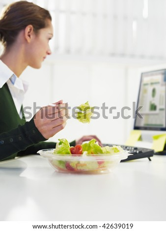 woman eating salad in office. Copy space - stock photo