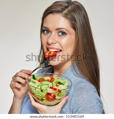 Woman eating salad. Isolated portrait of smiling girl eating healthy food.