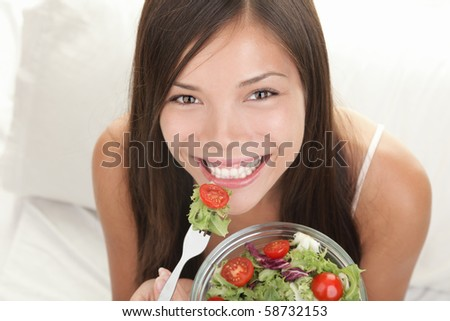 Woman eating salad. Portrait of beautiful smiling and happy mixed Asian Caucasian woman enjoying a healthy salad and cherry tomatoes snack. - stock photo