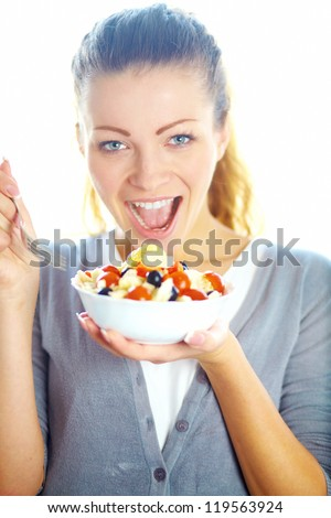 Woman eating salad. Portrait of beautiful smiling and happy woman