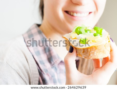 Woman eating sandwich with cheese and green vegetables onion  - stock photo