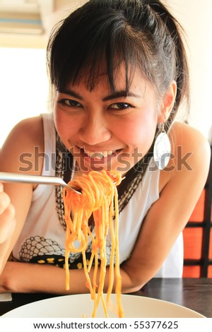 woman eating spaghetti in restaurant - stock photo