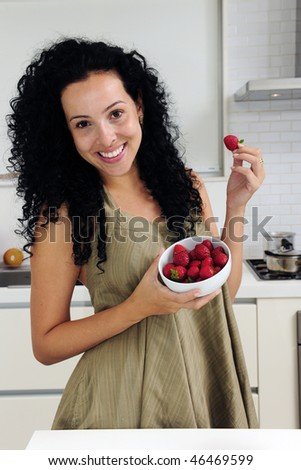 Woman eating strawberries in a modern kitchen - stock photo