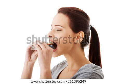 Woman eating too many pills. - stock photo