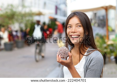 Woman eating traditional danish food floedeboller also called cream buns or marshmallow teacake. Girl enjoying the chocolate covered treat outside in city street of Copenhagen, Denmark. - stock photo