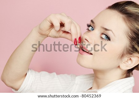 woman eats tablet against the pink background - stock photo