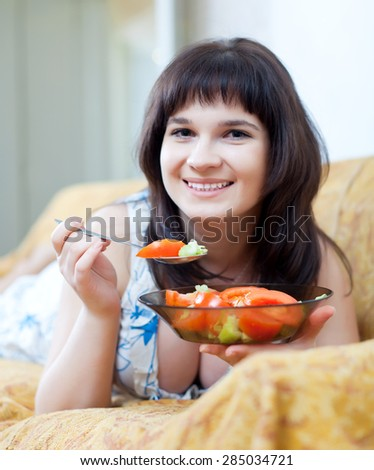 woman eats tomatoes salad at home