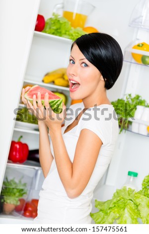 Woman eats watermelon near the opened refrigerator full of vegetables and fruit. Concept of healthy and dieting food - stock photo