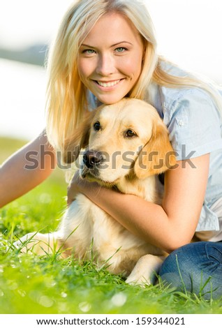Woman embraces golden retriever lying on the green grass - stock photo