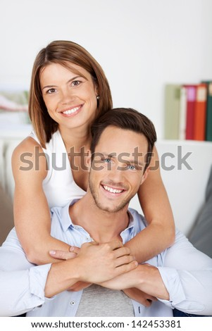 Woman embracing her husband at the back in the living room - stock photo