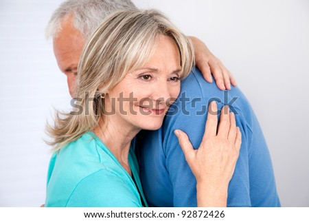 Woman embracing her husband with smile - stock photo