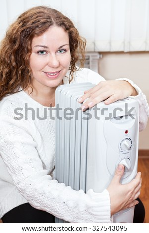 Woman embracing radiator trying to heat up in domestic room - stock photo
