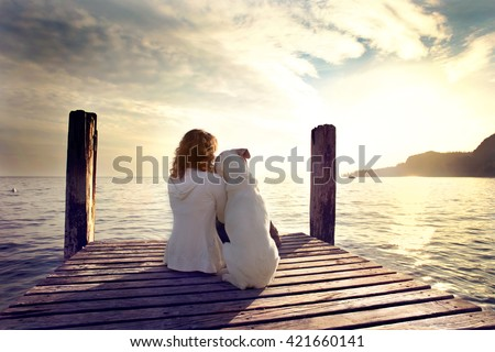 woman embracing sweetly his dog while looking the view - stock photo
