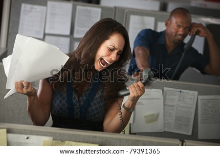Woman employee yells on phone in her cubicle - stock photo