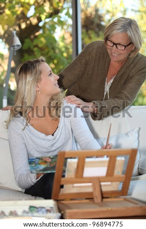 Woman encouraging a young painter at home - stock photo