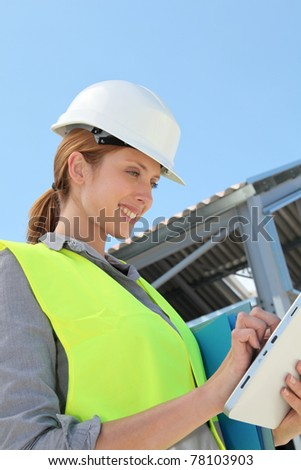 Woman engineer checking building plan on touchpad - stock photo