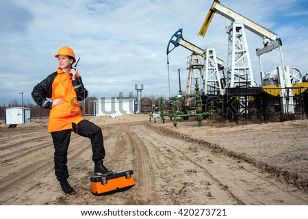 Woman engineer in the oil field talking on the radio wearing orange helmet and work clothes. Industrial site background. - stock photo