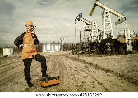 Woman engineer in the oil field talking on the radio wearing orange helmet and work clothes. Industrial site background. Toned. - stock photo
