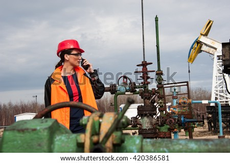 Woman engineer in the oil field talking on the radio wearing red helmet and orange work clothes. Industrial site background. - stock photo