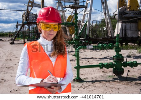 Woman engineer in yellow glasses on the oil field wearing red helmet and work clothes. Industrial site background. - stock photo