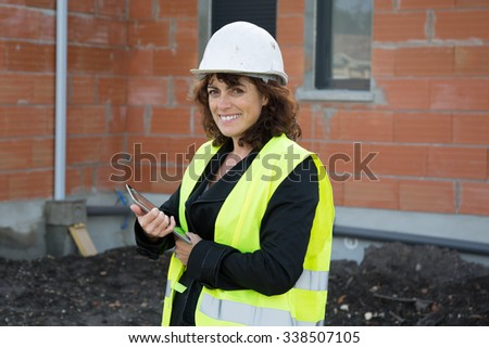 Woman engineer on building site using a tablet