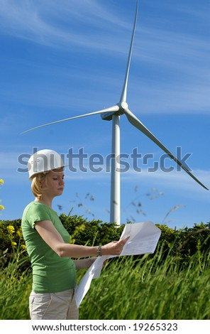 Woman engineer or architect with white safety hat and wind turbines on background - stock photo