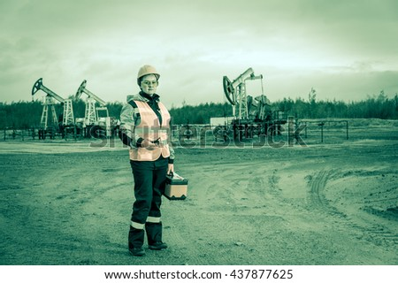 Woman engineer with radio phone and toolbox in the oil field wearing orange helmet and work clothes. Industrial site background. Toned. - stock photo
