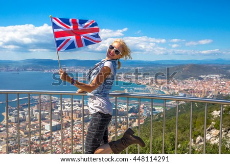 Woman enjoy with the British flag in hand on top of Gibraltar Rock. - stock photo