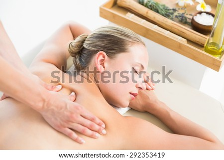 Woman enjoying a back massage at the health spa - stock photo