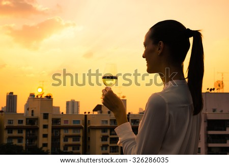 Woman enjoying a glass of wine in the city.  - stock photo