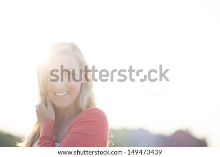 Woman enjoying a hot summer day standing smiling at the camera with a bright sunburst over her shoulder and copy space.