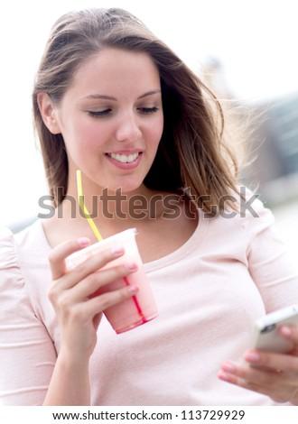 Woman enjoying a milkshake and texting on her phone - stock photo