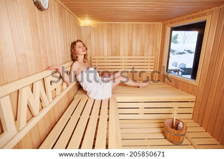 Woman enjoying a peaceful sauna on her own relaxing on the wooden bench above the water bucket and ladle with her eyes closed - stock photo