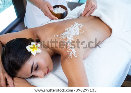Woman enjoying a salt scrub massage at spa - stock photo