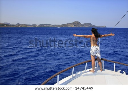 Woman enjoying a sunny summer day on a boat; position inspires freedom.