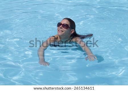 Woman enjoying a swim in swimming pool - stock photo
