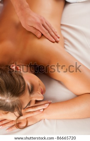Woman enjoying a wellness back massage in a spa, she is very relaxed (close-up) - stock photo
