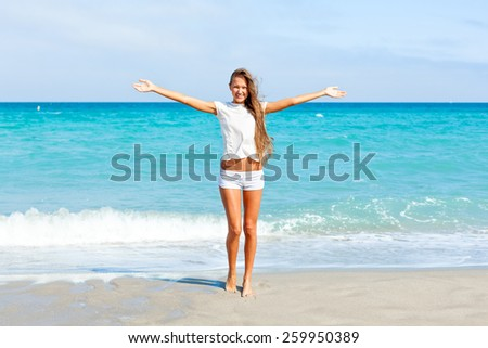 woman enjoying beautiful ocean view. girl standing on the beach with arms outspread. - stock photo