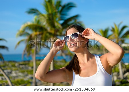Woman enjoying caribbean vacation travel. Caucasian brunette wearing sunglasses towards palm trees. - stock photo