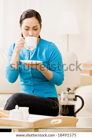 Woman enjoying drinking a cup of coffee in livingroom - stock photo