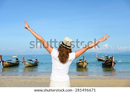 Woman enjoying freedom and having fun at Krabi, Thailand. Rear view of young brunette raising arms towards the sea at Railay Beach. - stock photo