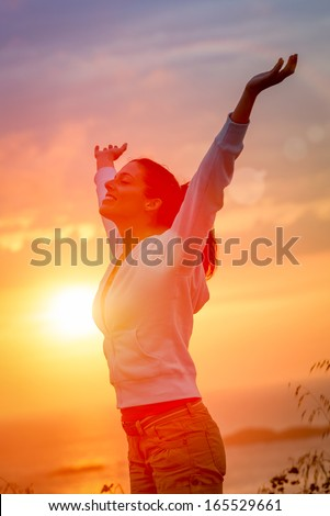 Woman enjoying freedom and life on beautiful and magical sunset. Blissful girl raising arms feeling free, relaxed and happy. - stock photo