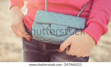 Woman enjoying freedom and life on beautiful and magical sunset. relaxed and happy. Fashion handbag - stock photo