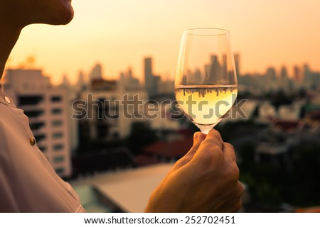 Woman enjoying glass of wine in the city - stock photo