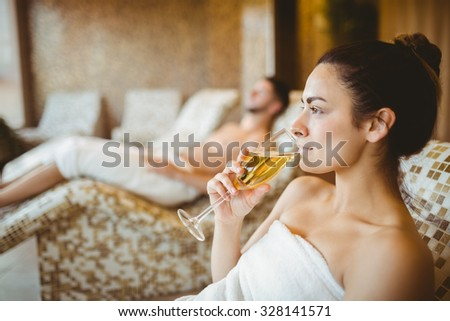 Woman enjoying her champagne at the spa - stock photo