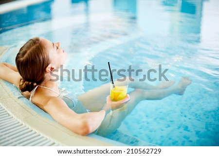 Woman enjoying in swimming pool after procedures - stock photo