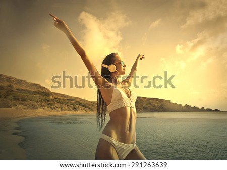 Woman enjoying music at the beach - stock photo