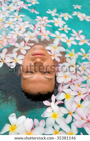 woman enjoying pure waters with beautiful plumeria flowers